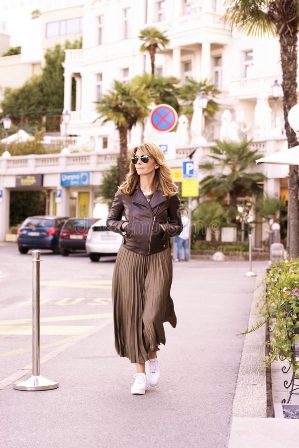 Attractive woman wearing fashionable clothes while walking on the street royalty free stock images