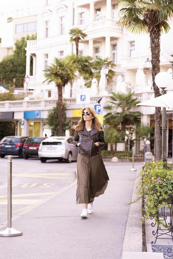 Attractive woman wearing fashionable clothes while walking on the street stock photography