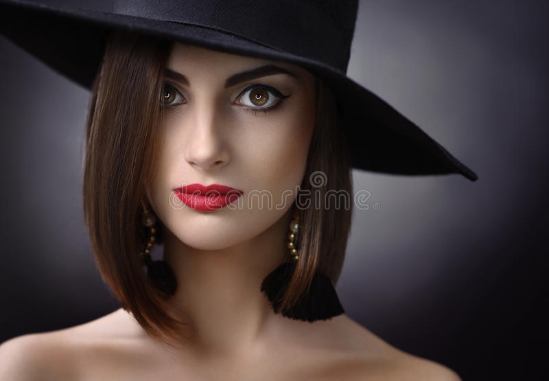 Attractive woman wearing a hat posing on black background. Close up studio portrait of a beautiful young brunette woman wearing evening makeup with red lips and royalty free stock photos