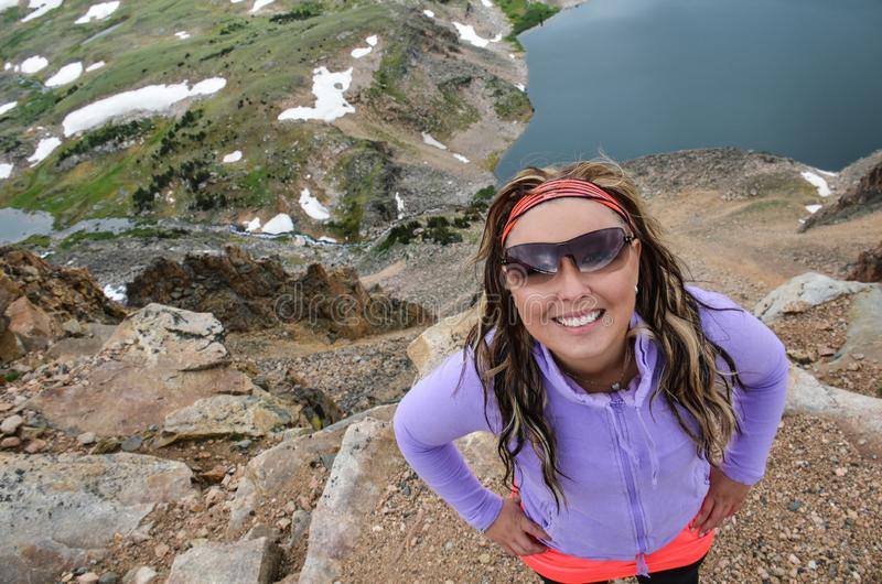 Attractive woman wearing sunglasses poses near an alpine lake in Montana. Attractive woman wearing sunglasses poses near an alpine lake along the Beartooth stock photography