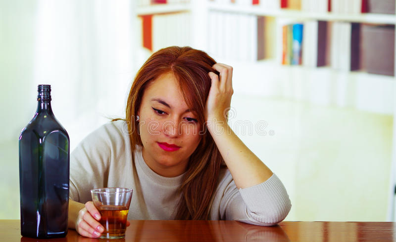 Attractive woman wearing white sweater sitting by bar counter lying over desk next to glass and bottle, drunk depressed royalty free stock images
