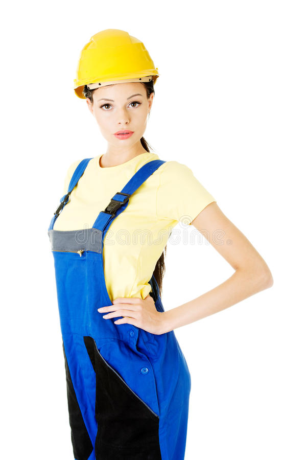 Attractive woman wears work clothes and helmet. royalty free stock photo