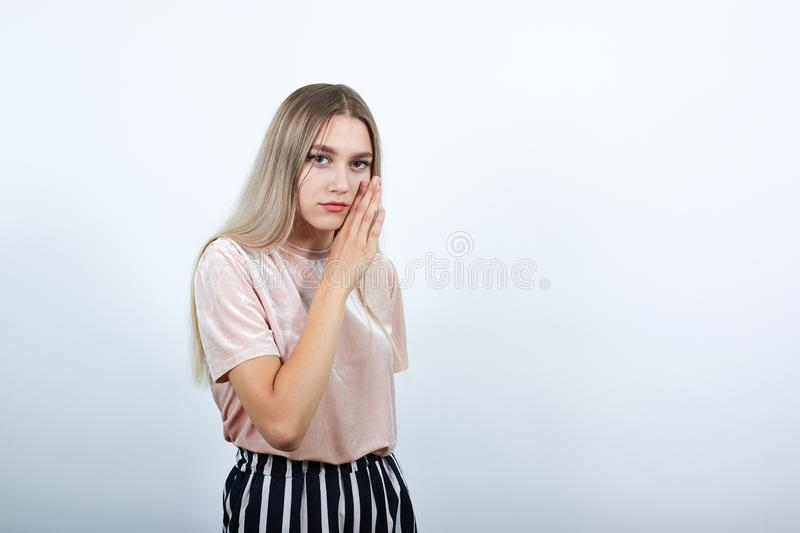 Attractive woman whispering something, keeping hand near mouth like gossip girl royalty free stock photo