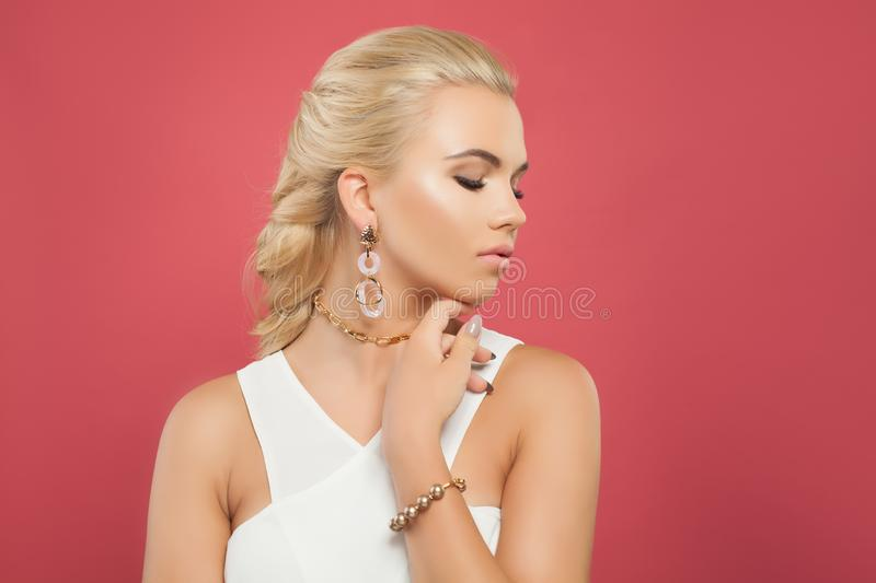 Attractive woman in white blouse and gold chain necklace, earrings and bracelet on bright pink background.  stock photo