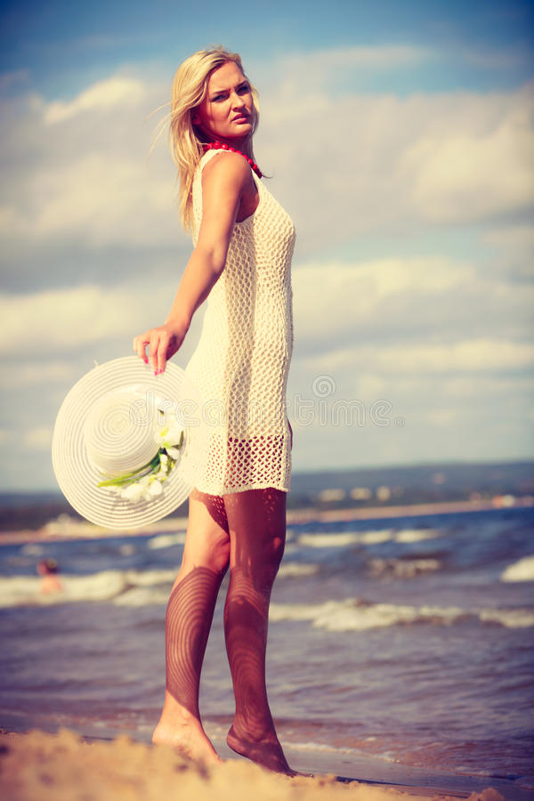 Attractive woman with white dress. Clothing, summer time concept. Attractive woman with white dress. Lady enjoying sunny weather by the seaside royalty free stock photography