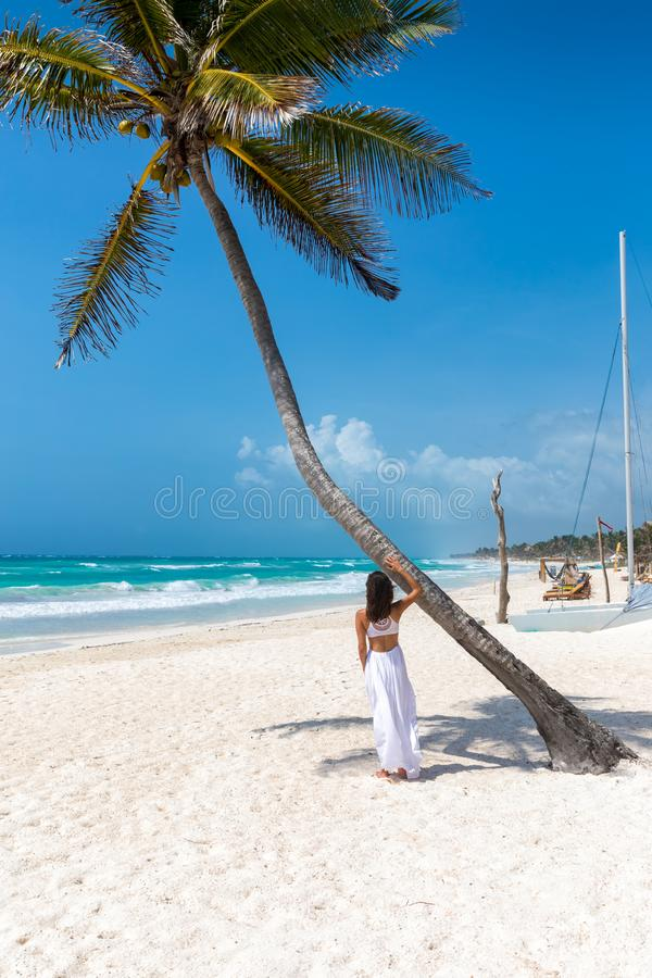 Woman standing next to a palm tree on a tropical beach in the caribbean, Mexico stock photo