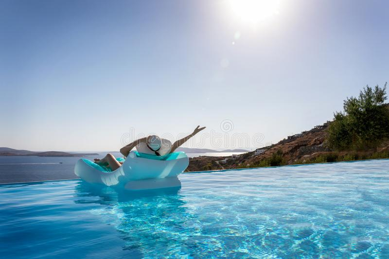 Woman enjoys the view to the Mediterranean sea floating on a infinity pool. Attractive woman with a white hat floats on a infinity pool and enjoys the view to stock image