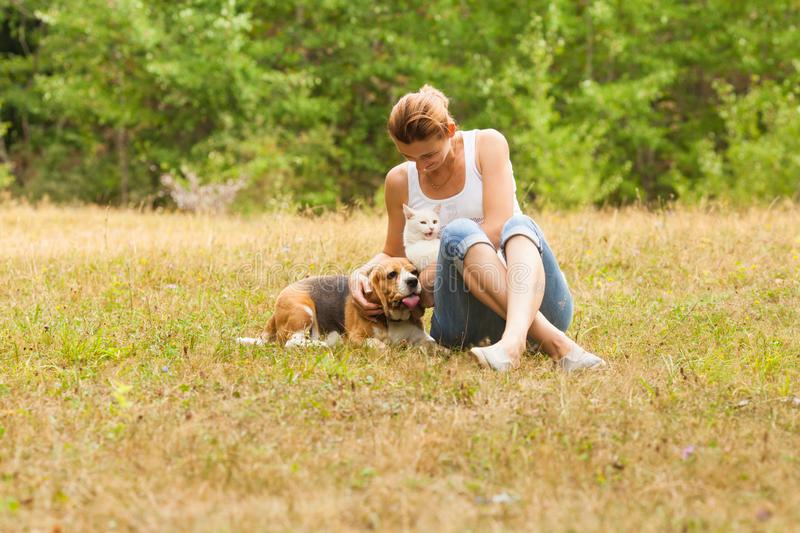 Portrait of woman sitting on grass near her dog and cat royalty free stock photos