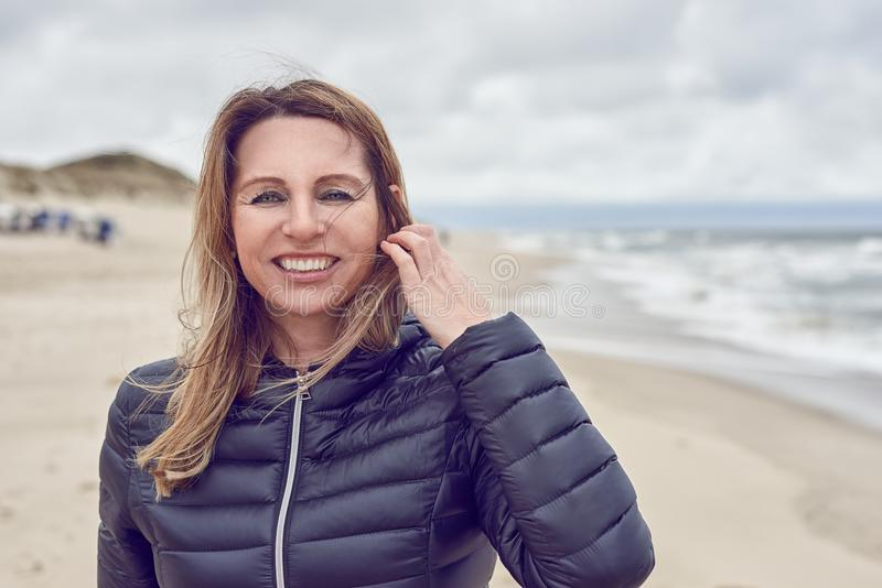 Attractive woman on a windswept beach on a cloudy day royalty free stock photo