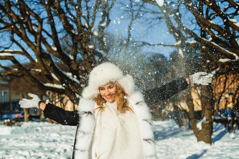 Attractive woman in winter coat having fun with snow. Outdoors royalty free stock image