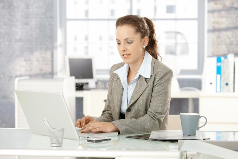 Attractive woman working on laptop in office royalty free stock image