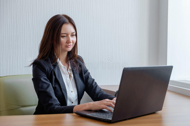 Attractive woman working in office on laptop.  royalty free stock photography