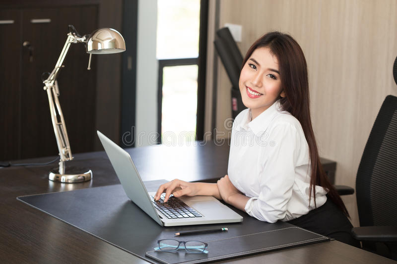 Attractive woman working in office on laptop royalty free stock photo