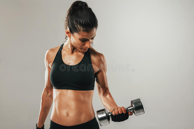 Attractive woman working out with dumbbells. Attractive young woman with a fit toned body working out with dumbbells lifting weights to strengthen her abdominal royalty free stock photos