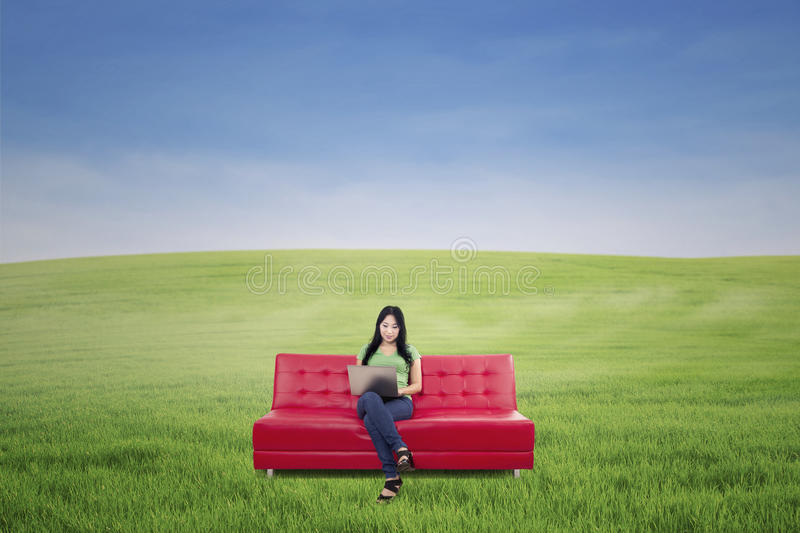 Attractive Woman Working On Red Sofa Outdoor Royalty Free Stock Photo
