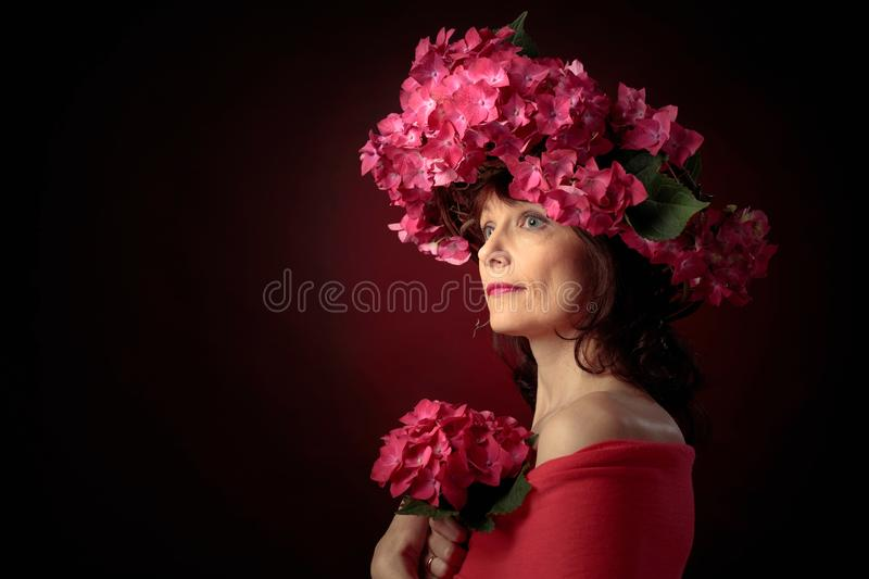Attractive woman in wreath with coral hydrangea blossoms. Mature woman with blooming flowers. Copy space stock image