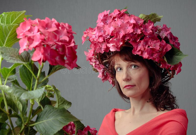 Attractive woman in wreath with coral hydrangea blossoms. Mature woman with blooming flowers royalty free stock image