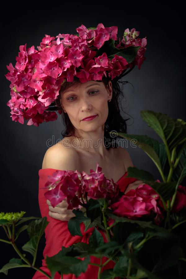 Attractive woman in wreath with coral hydrangea blossoms. Mature woman with blooming flowers stock photo