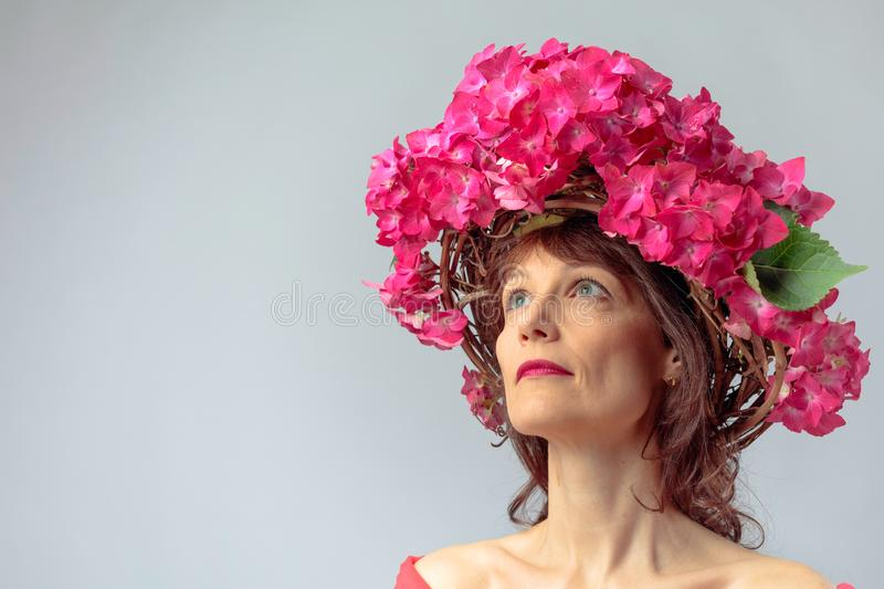 Attractive woman in wreath with coral hydrangea blossoms. Mature woman with blooming flowers. Copy space stock photography