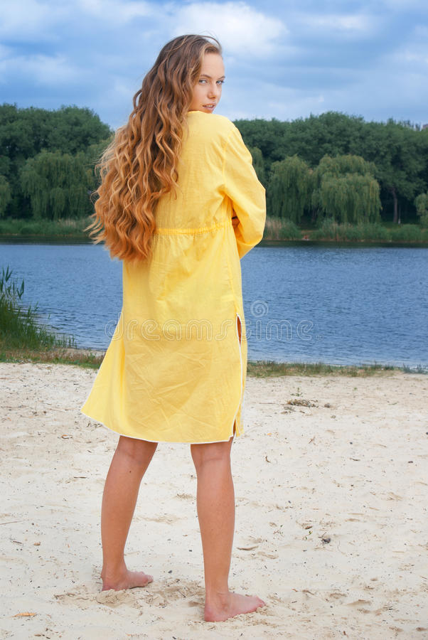 Attractive woman in yellow outfit on river beach stock photos