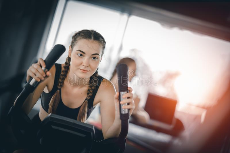Attractive woman biking in the gym, exercising legs doing cardio workout cycling bikes. Fitness club with training exercise bikes stock images