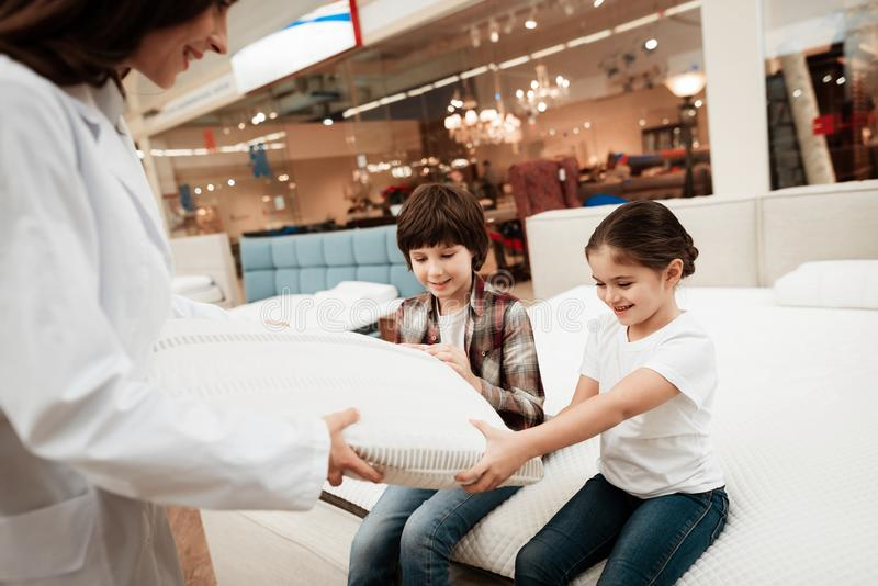 Attractive woman dressed in white robe shows orthopedic pillow to young children sitting on mattress. Attractive women dressed in white robe shows orthopedic royalty free stock photos