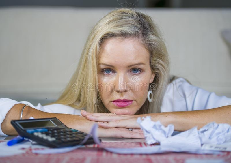 Worried and desperate blond woman calculating domestic money expenses doing paperwork and bank bills accounting with calculator su stock photography