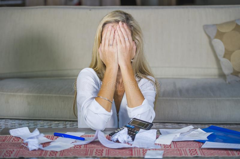 Attractive worried and desperate blond woman calculating domestic money expenses doing paperwork and bank bills accounting. With calculator suffering stress in royalty free stock photos