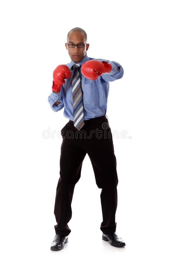 Attractive young African American businessman. Wearing boxing gloves. Blow with left arm. Studio shot. White background royalty free stock photography