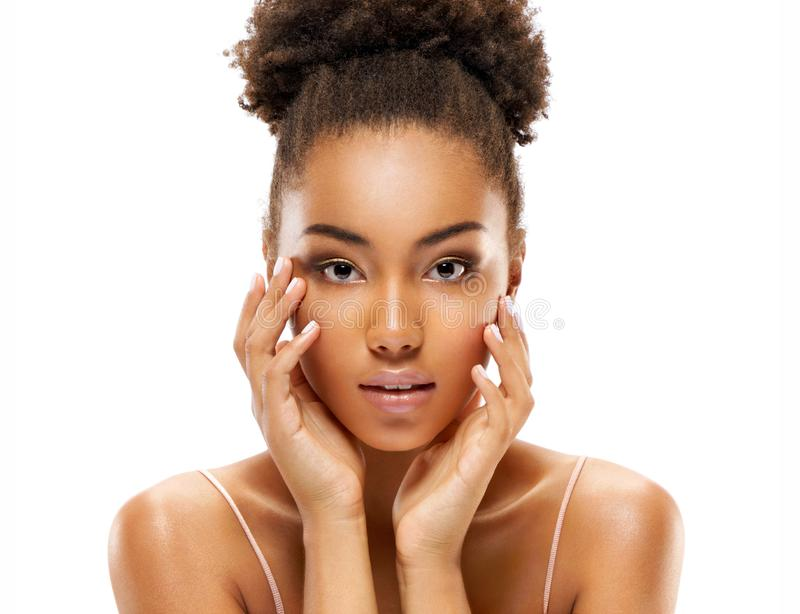 Attractive young african american girl touching her face on white background. Beauty & Skin care concept royalty free stock image