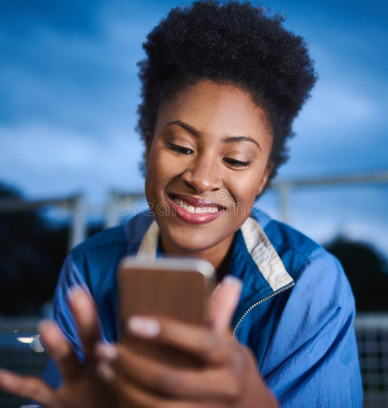 Attractive young african american woman skaterboarder using a mo. Portrait of a edgy black girl with an afro using a smartphone to message friends while sitting royalty free stock photo