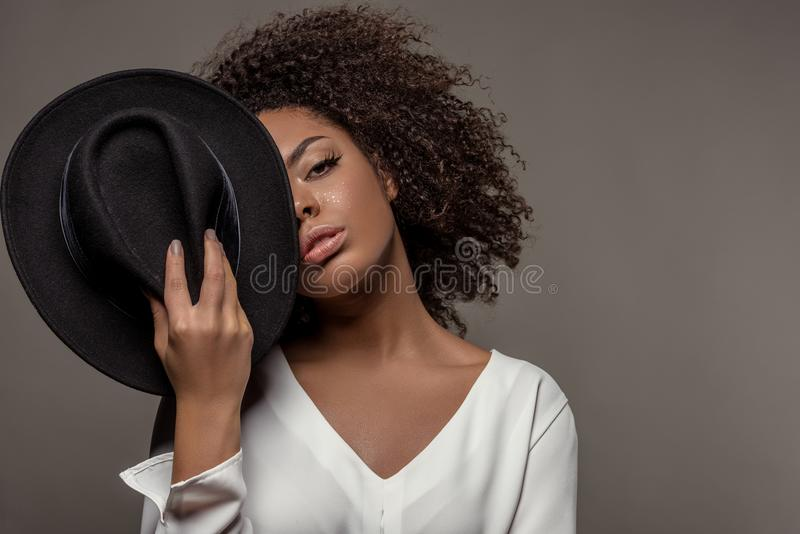 Attractive young african american woman in white shirt holding black hat over half of her face stock photo