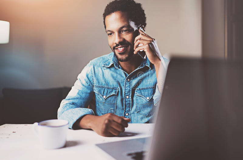 Attractive young African man talking by smartphone while sitting at the wooden table his modern home.Concept of young royalty free stock photos