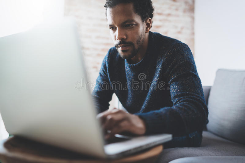 Attractive young African man using laptop while sitting at his modern coworking place.Concept of business people full stock images