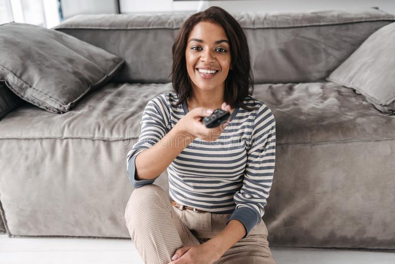 Attractive young afro american woman sitting on a couch stock photos