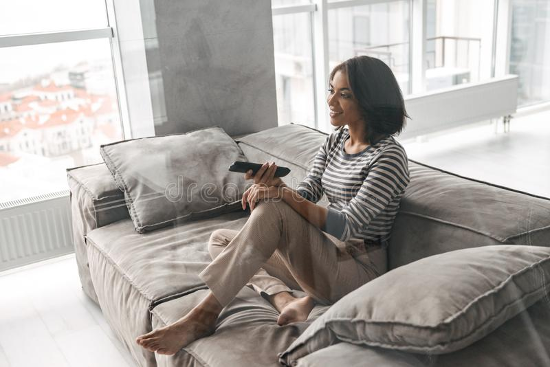 Attractive young afro american woman. Sitting on a couch at home, watching TV, holding remote control stock image