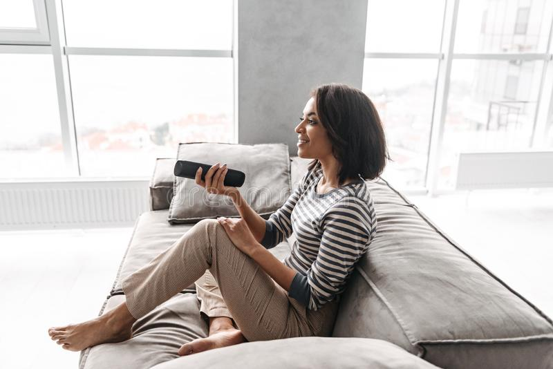 Attractive young afro american woman. Sitting on a couch at home, watching TV, holding remote control stock photos