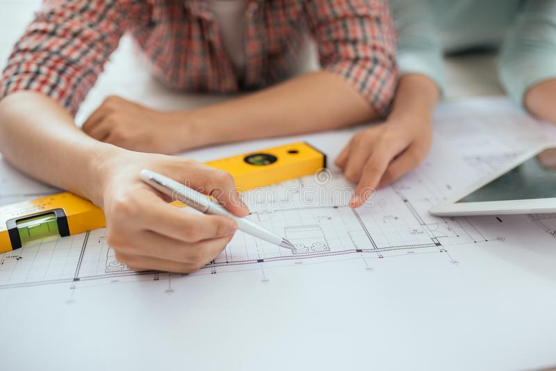 Attractive young asian adult couple looking at house plans. stock image