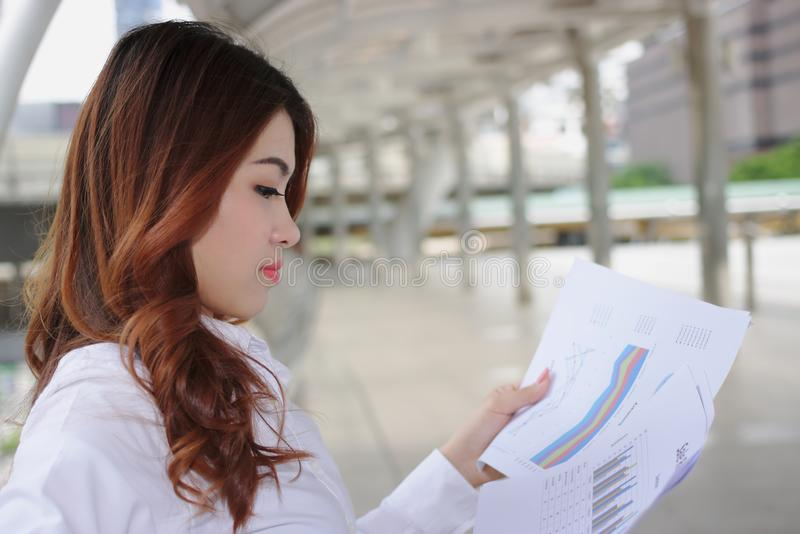 Attractive young Asian business woman analyzing charts or paperwork at outside office. Selective focus and shallow depth of field. stock images