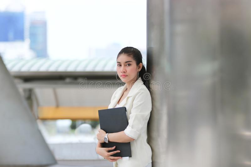Attractive young Asian business woman with binder standing at outside office royalty free stock photo