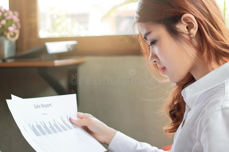 Attractive young Asian business woman looking paperwork or charts on the desk with sunshine effect. royalty free stock image