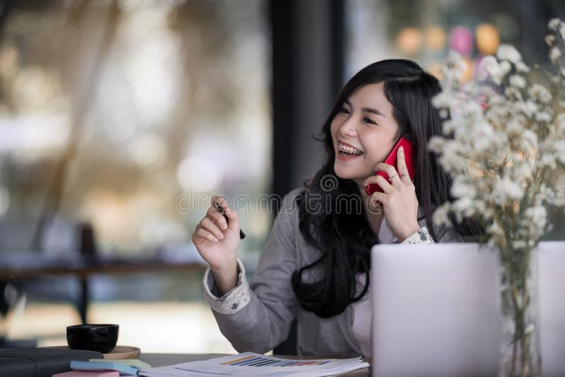 Attractive young asian business woman talking on the mobile phone and smiling while sitting at her working place in office royalty free stock image