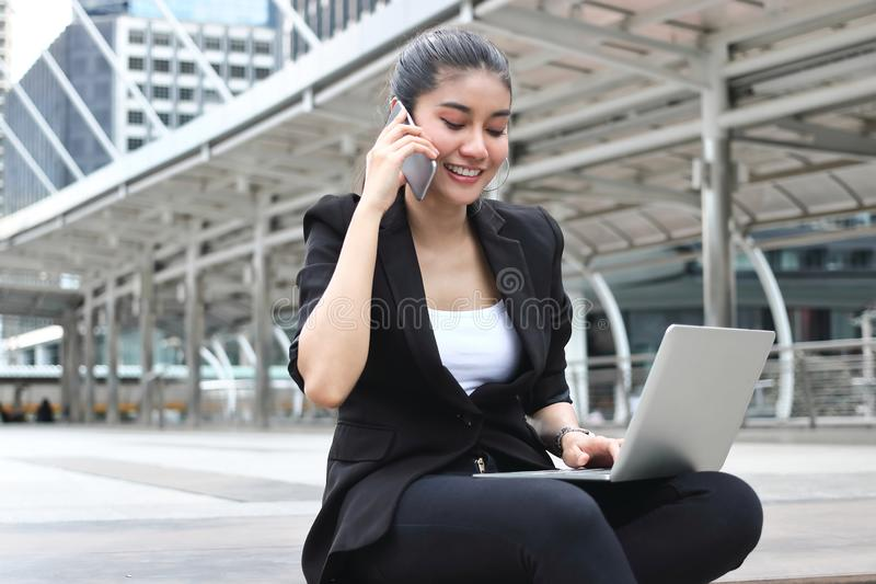 Attractive young Asian business woman working with laptop and mobile smart phone at outside office stock photography