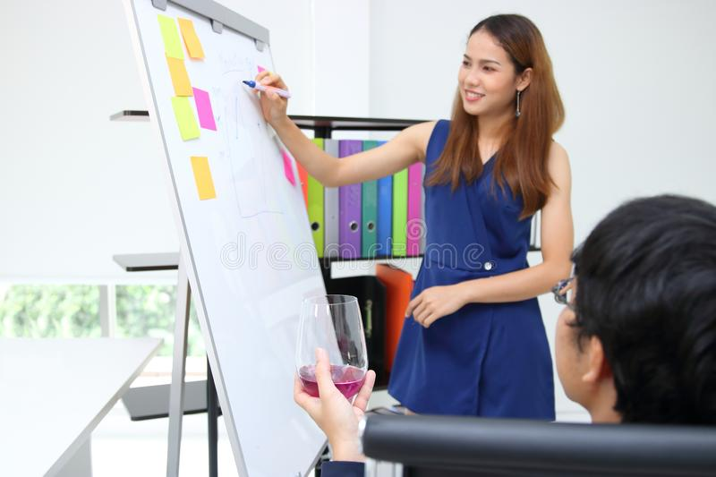 Attractive young Asian business woman explaining strategies on flip chart to executive in boardroom royalty free stock photos