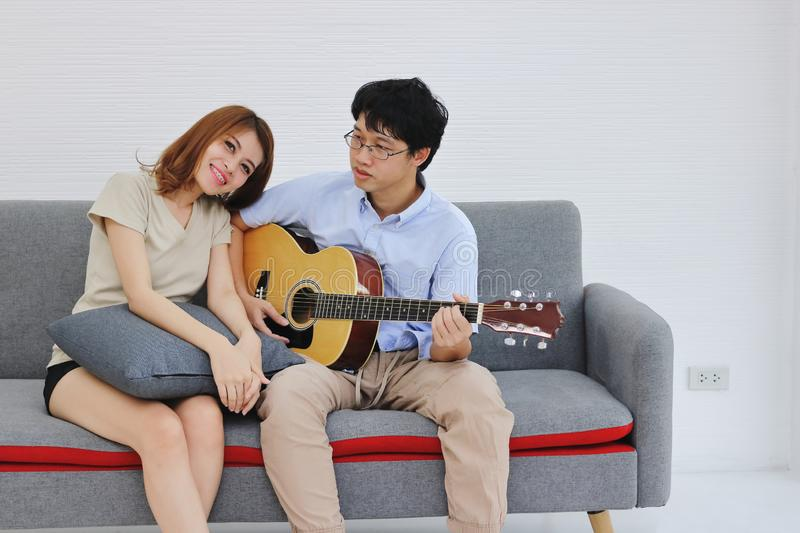 Attractive young Asian couple playing acoustic guitar together in living room. Love and romance people concept.  royalty free stock images