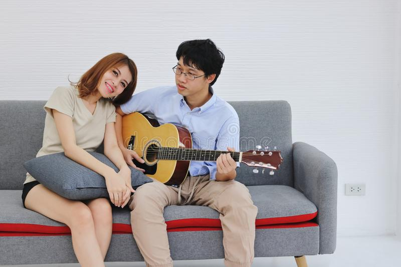 Attractive young Asian couple playing acoustic guitar together in living room. Love and romance people concept.  stock images