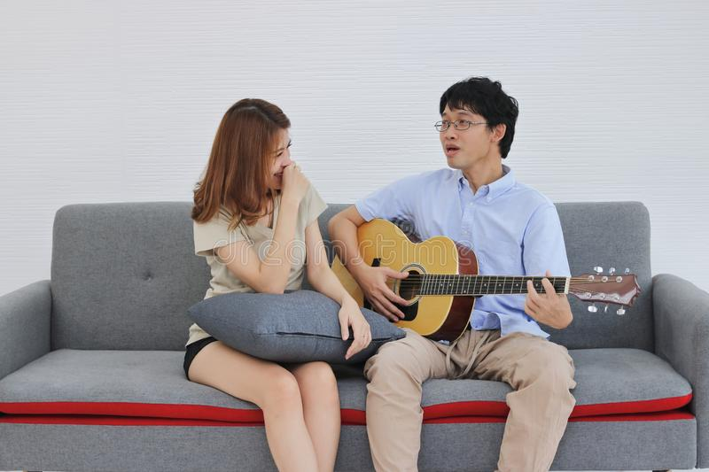 Attractive young Asian couple playing acoustic guitar together in living room. Love and romance people concept stock photo