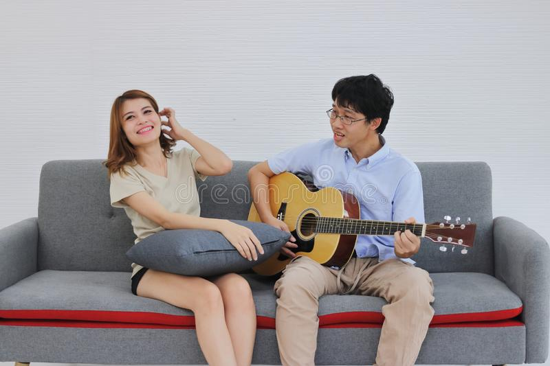 Attractive young Asian couple playing acoustic guitar together in living room. Love and romance people concept stock photos
