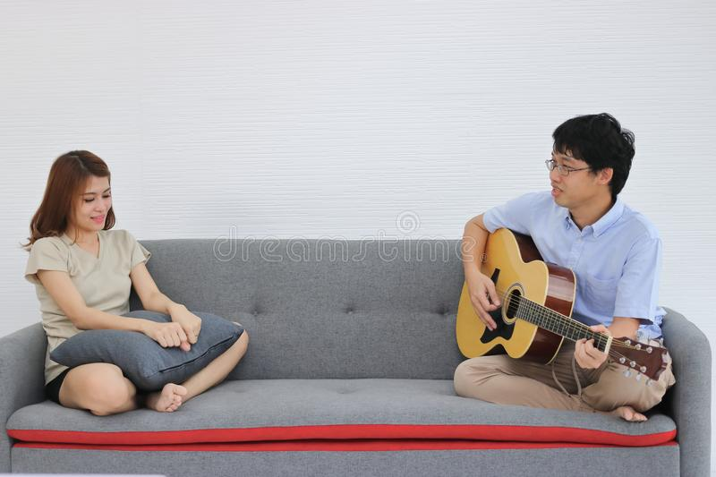 Attractive young Asian couple playing acoustic guitar together in living room. Love and romance people concept stock image