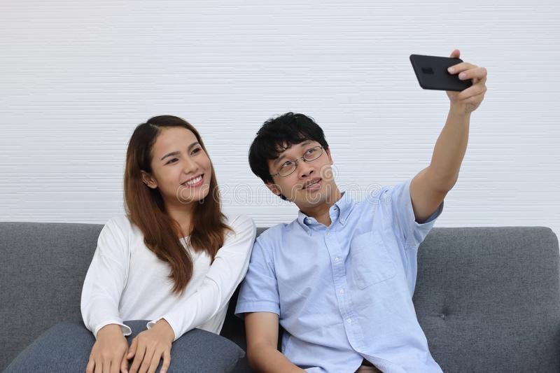 Attractive young Asian couple taking a photo or selfie together in living room. Love and romance people concept. stock photos